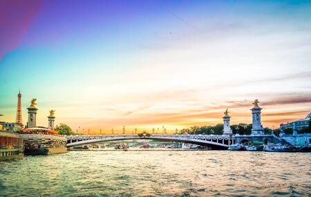 famouse Alexandre III Bridge at night, view over river Seine, Paris, France, retro toned