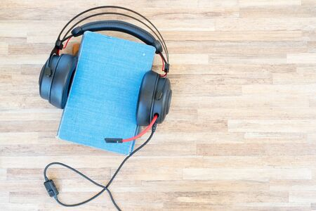 Audio book concept. Black headphones and pile of books on wooden table. Top view with copy space.