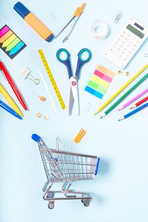 Back to school concept with school supplies falling in metalic cart on blue background with copy space