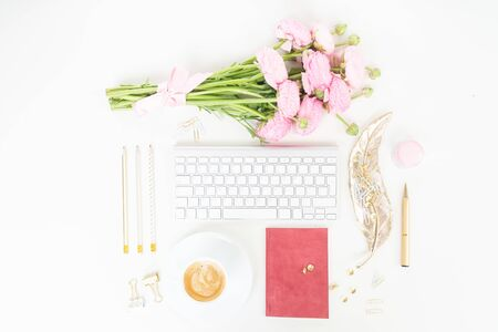 Flat lay home office workspace - modern keyboard with female accessories and ranunculus flowers, copy space on white desk background