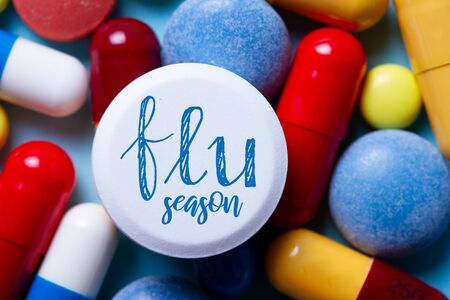Pile of colorful medical pills close up with flue season words