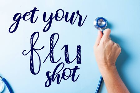 Healthcare concept - hand holding stethoscopee on blue background with get your flue shot words