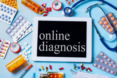 online healthcare concept - pile of medical pills with tablet screen on blue background, online diagnosis concept