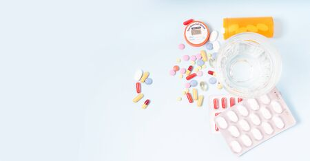 Coloful pills with glass of clear water close up over blue background, top view with copy space. Medical pharmacy concept, web banner format