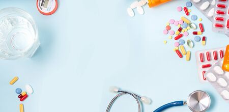 Colorful pills with glass of clear water over blue background, top view frame. Medical pharmacy concept, web banner format