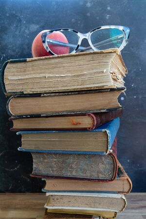 Stack of multicolored books, education, reading, back to school concept, glasses on the top Stockfoto