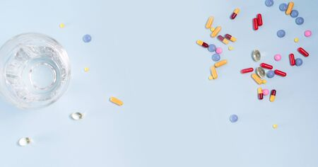 Coloful pills with glass of clear water over blue background with copy space, top view. Medical pharmacy concept, web banner format Reklamní fotografie