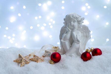 Noël blanc - ange mignon dans la neige, nuit bleue avec des lumières en arrière-plan. Concept de joyeux Noël et vacances. Banque d'images