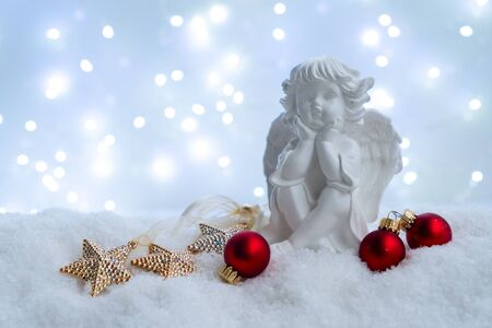 White christmas - cute angel in snow , blue night with lights in background. Happy Christmas and holidays concept. Stock Photo