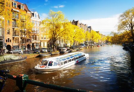 Facades of dutch houses over canal with saling boat, Amsterdam fall scenery, Netherlands Stock Photo