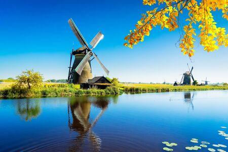 traditionelle holländische Windmühle mit Reflexion am Wasser, Kinderdijk am Herbsttag, Netherland