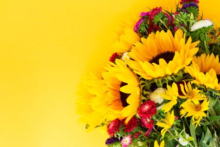 Sunflowers and aster fresh flowers, top view on yellow background, top view, natural fall flowers background