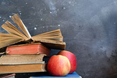 Stack of multicolored books with two apples, education, reading, back to school concept, copy space on blackboard