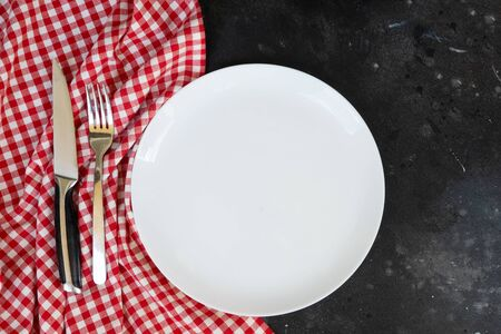 Abstract food background - empty white plate with napkin and cutlery