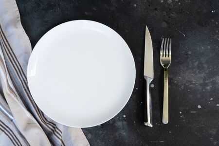 Abstract food background - empty white plate with napkin and cutlery, top view Stok Fotoğraf