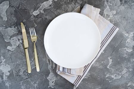 Abstract food background with white plate over gray kitchen table