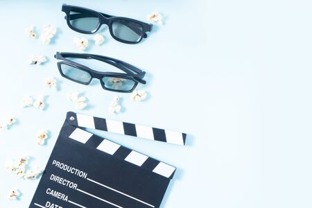 popcorn, cinema clapper and two pairs of 3d glasses over plain blue background, movie and cinema concept