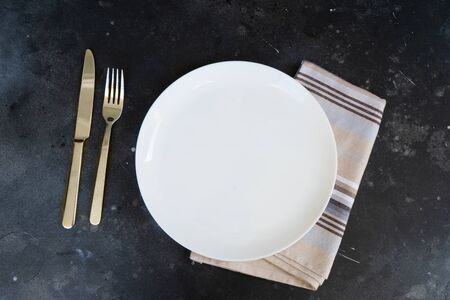 Abstract food background with white plate over black kitchen table Stok Fotoğraf