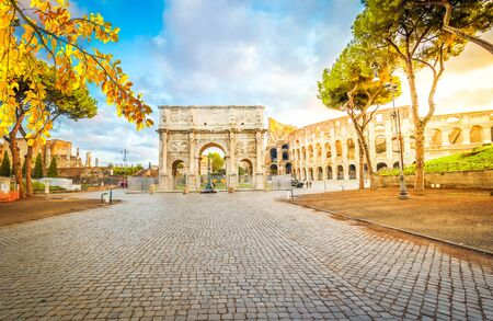 Arch of Constantine and Colosseum with empty alley road, antique Rome city, Italy at fall
