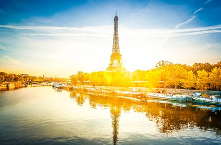 Paris Eiffel Tower reflecting in river Seine at sunrise in Paris, France. Eiffel Tower is one of the most iconic landmarks of Paris at fall