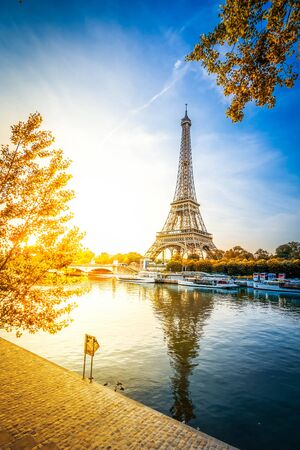 Paris Eiffel Tower and river Seine at sunrise in Paris, France. Eiffel Tower is one of the most iconic landmarks of Paris at fall