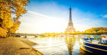 Paris Eiffel Tower reflecting in river Seine at sunrise in Paris, France. Web banner format. Eiffel Tower is one of the most iconic landmarks of Paris at fall