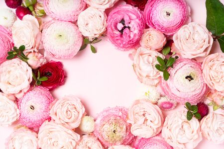 Flowers composition. Frame wreath made of roses and ranunculus flowers on pink background. Flat lay, top view with copy space
