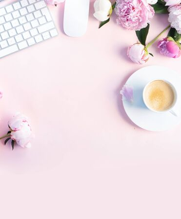 Flat lay home office workspace - modern keyboard with female accessories and fresh peony flowers, copy space on pink desk background
