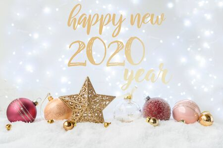 White christmas with snow - pink and golden decorations with stra over bokeh lights 2020 happy new year greetings