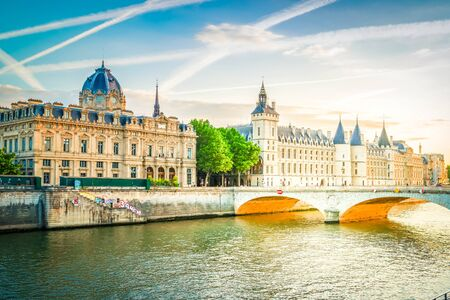 La Consiergerie - ex royal residence, Paris and Seine river with tour boat at sunny summer sunset, Paris, France, toned