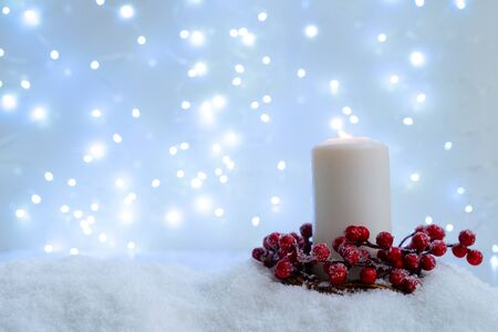 White christmas - glowing candle in snow, blue night with lights in background. Happy Christas and holidays concept.