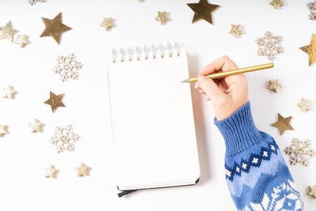 Wish list for Cristmas and New Year. Holiday decorations and ruled notebook with wish list on white desk, flat lay top view