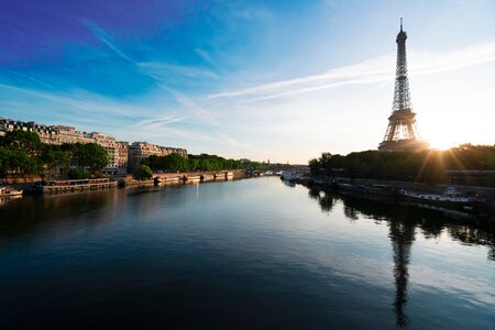 Paris Eiffel Tower and city of Paris reflecting in river Seine at sunrise in Paris, France. Eiffel Tower is one of the most iconic landmarks of Paris.