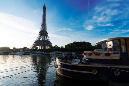 Paris Eiffel Tower reflecting in river Seine at sunrise with moored boats in Paris, France. Eiffel Tower is one of the most iconic landmarks of Paris.