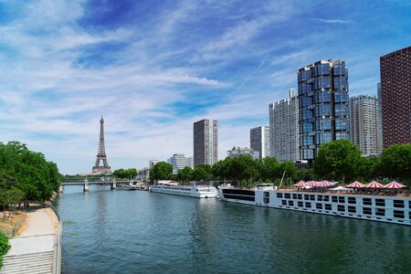 Eiffel Tower with moden houses over Seine at summer, Paris, France