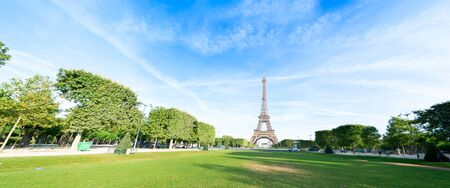 Paris Eiffel Tower over green grass lane in Paris, France. Web banner format. Eiffel Tower is one of the most iconic landmarks of Paris. 스톡 콘텐츠