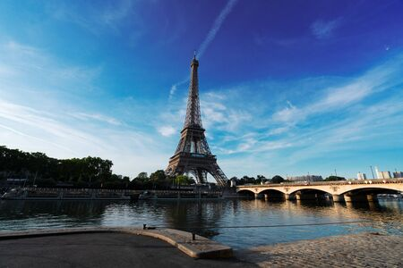 Paris Eiffel Tower reflecting in river Seine with bridge Pont dIena in Paris, France. Eiffel Tower is one of the most iconic landmarks of Paris. 스톡 콘텐츠