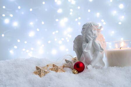 Noël blanc - ange mignon dans la neige, nuit bleue avec des lumières