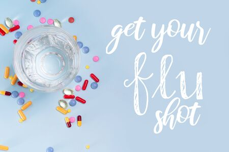 Coloful pills with glass of clear water over plain blue background. Get your flue shot concept