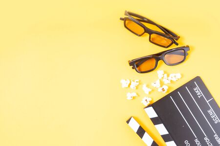 popcorn, cinema clapper and two pairs of 3d glasses over yellow background, movie and cinema concept