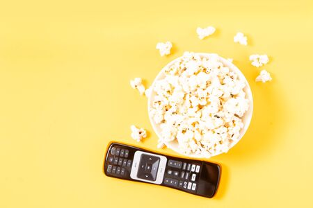 bowl of popcorn, nd remote control for TV over yellow background, movie and cinema concept
