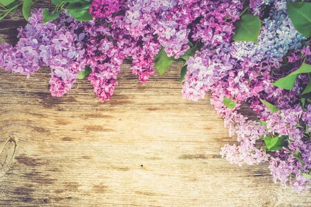 Fresh lilac flowers over wooden background with copy space, flat lay floral composition with copy space, toned 免版税图像