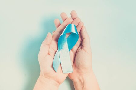 Hand holding Diabetes Awareness Blue Ribbon on plain blue background. World Diabetes Day concept, toned