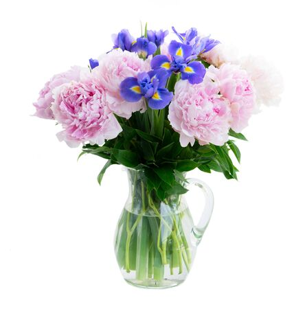 Fresh peony and iris flowers in glass vase isolated on white background
