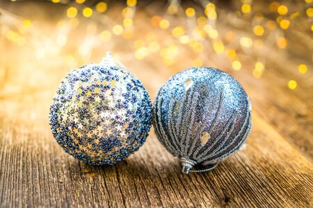Two gray christmas balls on natural wood background, toned