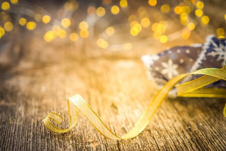 christmas scene with blue and golden ribbon and bokeh lights on natural wood background, toned