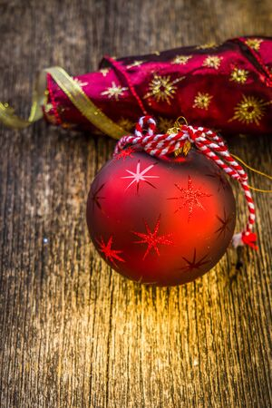 christmas scene with red and golden decorations and bokeh lights on natural wooden background, toned
