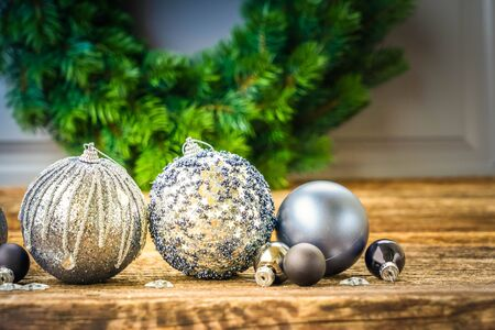 Gray christmas balls on natural wooden table background, toned