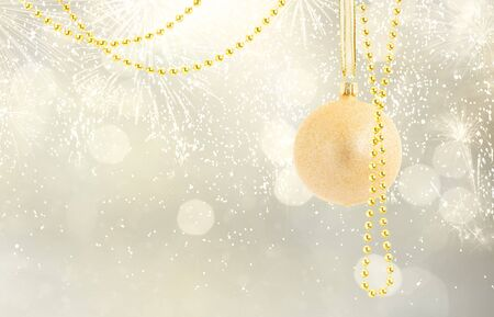 Hanging golden christmas balls with garlands on silver bokeh background with copy space