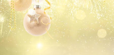 Hanging golden christmas balls on golden bokeh background web banner with copy space